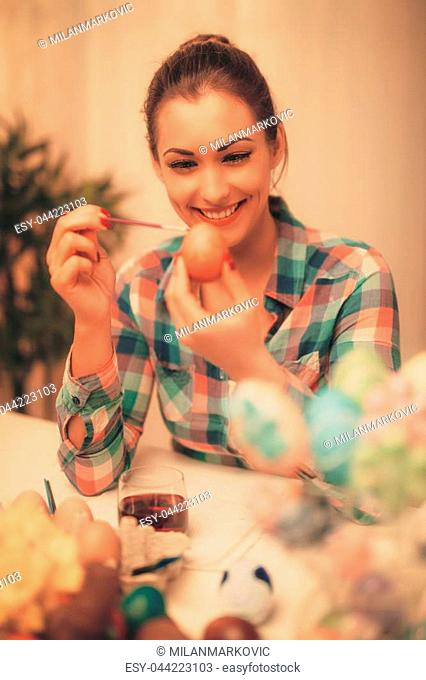 Beautiful smiling young woman painting Easter egg at home
