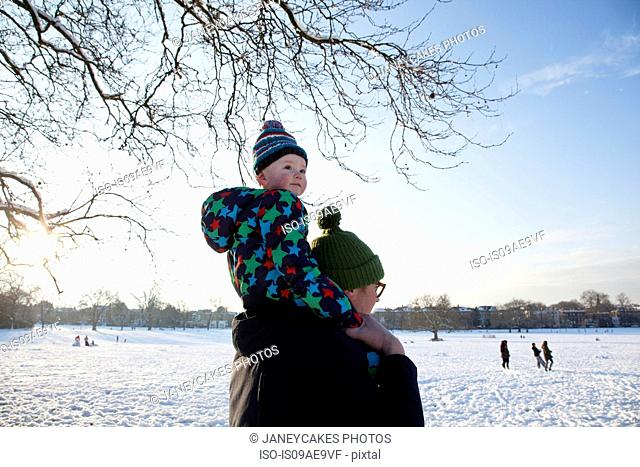 Father carrying child on shoulder in park