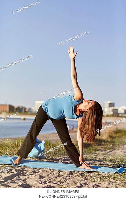 Pregnant woman practicing yoga at seaside