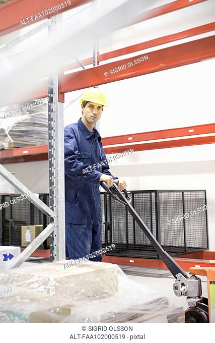 Worker operating pallet jack in warehouse