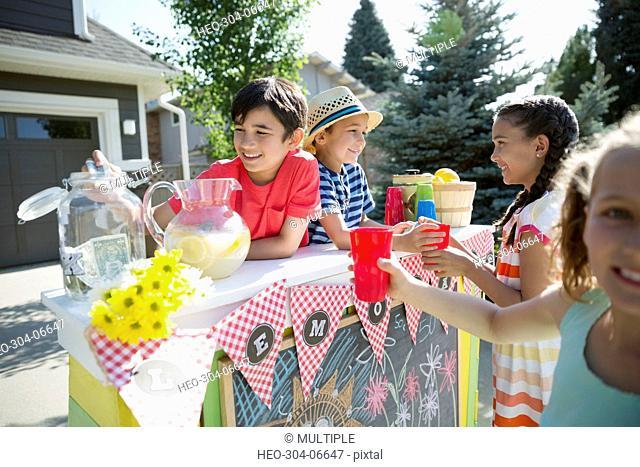 Girls buying lemonade from boys at lemonade stand in sunny driveway