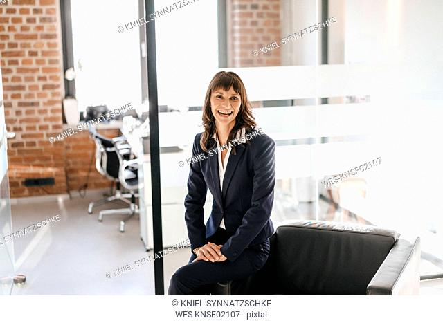 Successful businesswoman sitting on armchair