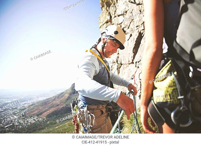 Male rock climber adjusting ropes