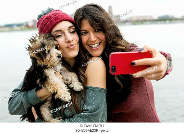 Friends holding pet dog for photograph
