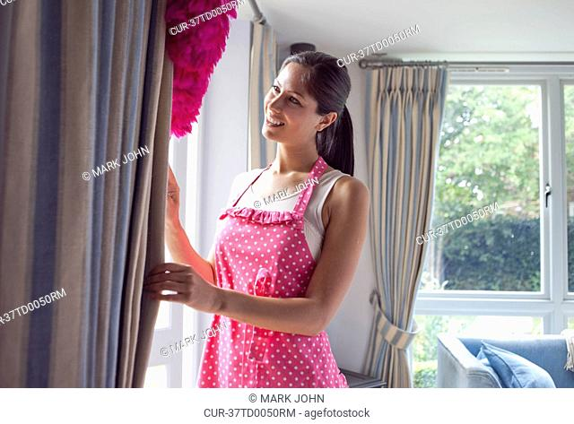 Woman dusting curtains in living room