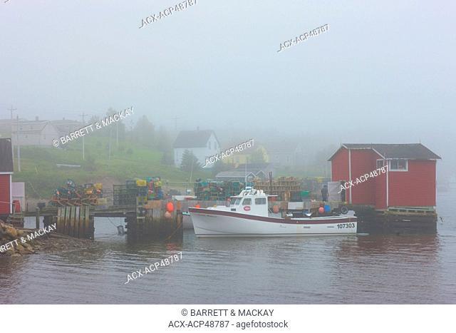 Fishing boats docked at wharf in fog, Louisbourg, Cape Breton, Nova Scotia, Canada