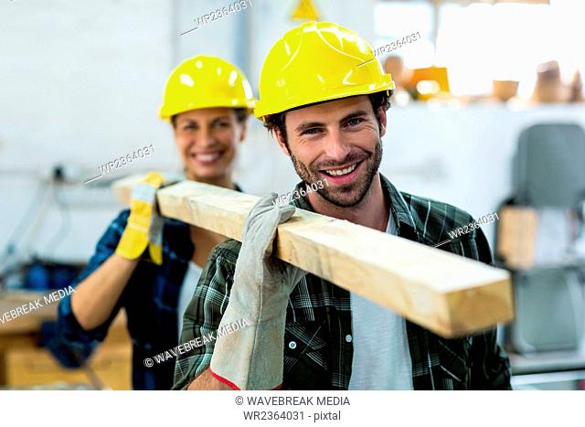 Male and female carpenters holding a wooden plank in workshop