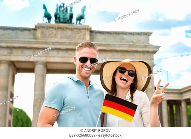 Portrait Of Young Happy Couple With German Flag Standing At Brandenburg Gate