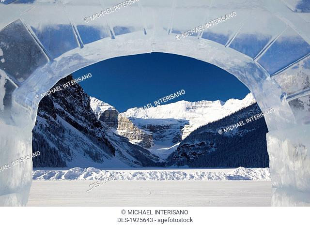 snow covered mountain and frozen lake framed in a ice castle window, lake louise, alberta, canada