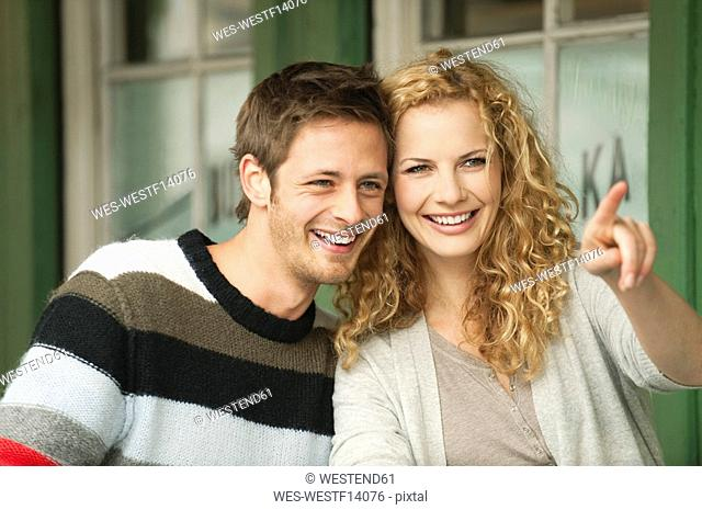 Germany, Bavaria, Munich, Young couple at Viktualienmarkt, woman pointing, smiling, portrait