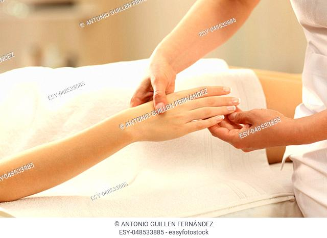Close up of a woman receiving a hand massage from a therapist in a spa