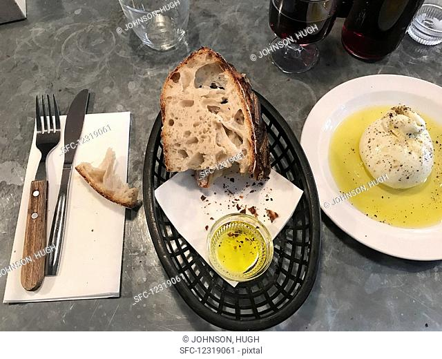 Sourdough bread with olive oil on a restaurant counter (Italy)