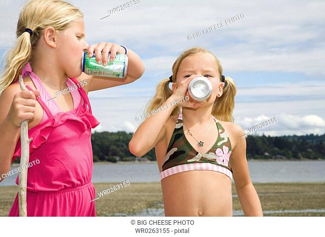 Two girls drinking soda