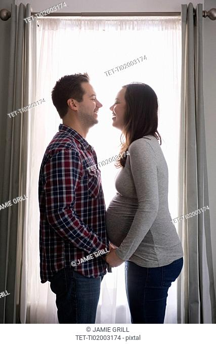 Mid adult couple in front of window, laughing