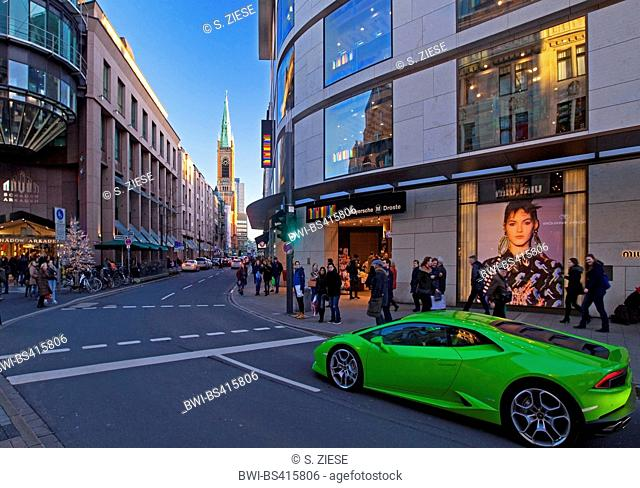 green sports car in the city with Schadow Arkaden and Johanniskirche, Germany, North Rhine-Westphalia, Duesseldorf