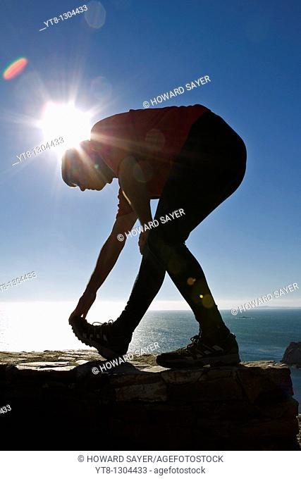 Man performing stretching exercise by the sea