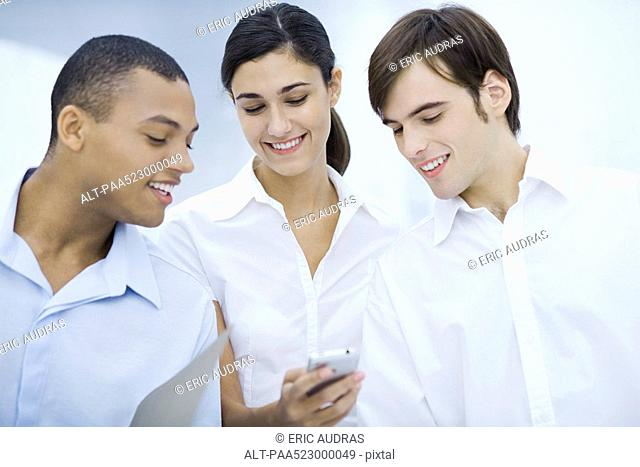 Three young professionals looking at cell phone together, smiling