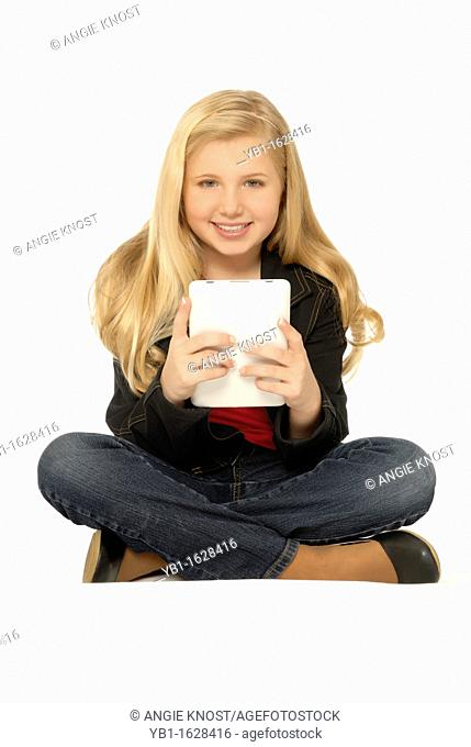 Ten year old girl sitting and using a tablet computer  She is smiling and looking at the viewer