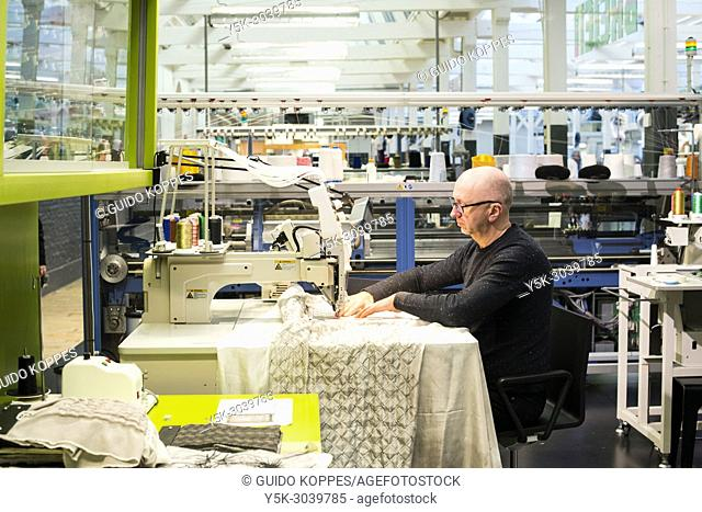 Tilburg, Netherlands. Middle aged caucasian male wearing glasses working behind his industrial scale sewing machine inside a former Texitile Factory