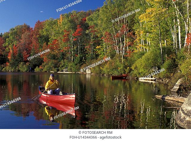 canoeing, canoe, Vermont, VT, Woman paddles a red canoe on the calm waters of Kettle Pond in Groton State Forest in the fall