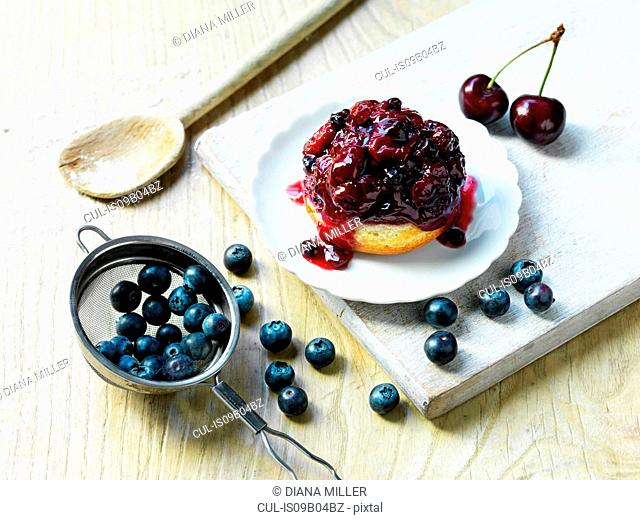 Morello cherry and blueberry sponge, fresh cherries and blueberries, wooden spoon with flour, white washed wooden board and wooden table