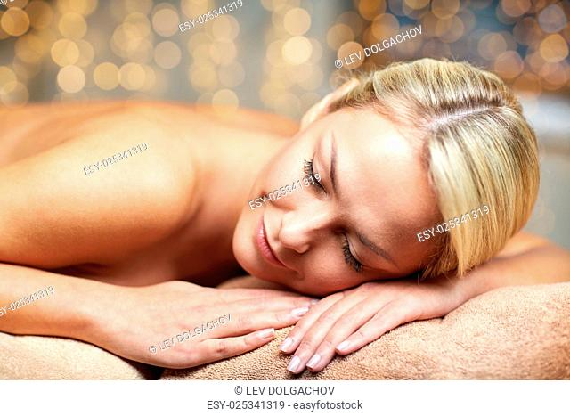 people, beauty, spa, healthy lifestyle and relaxation concept - close up of beautiful young woman lying on massage table in spa