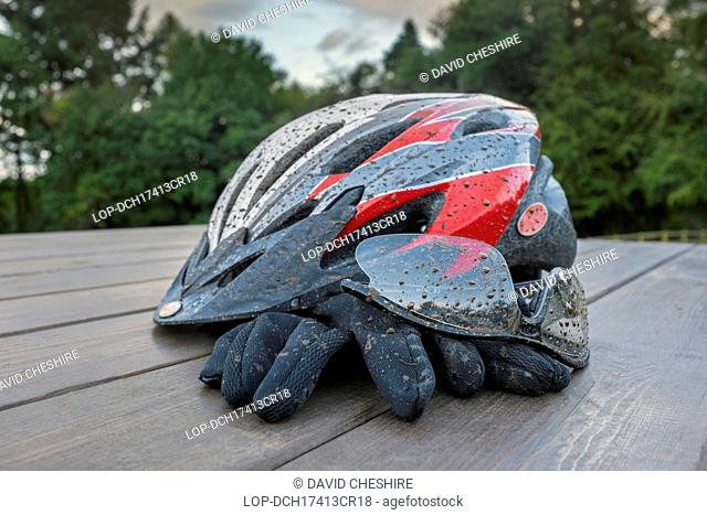 Wales, Monmouthshire, Monmouth. Mud spattered cycle helmet with glasses and gloves