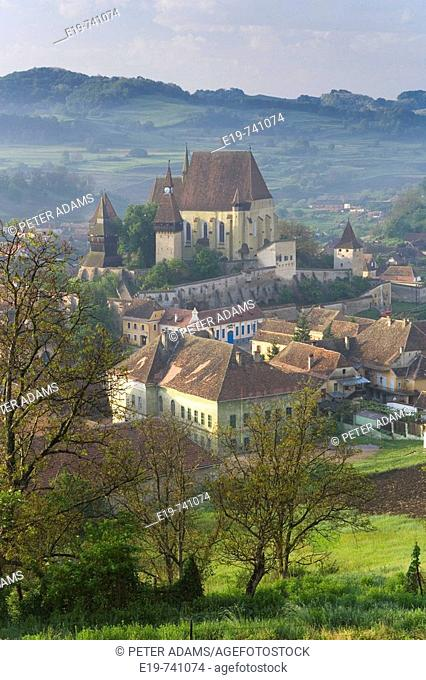 Biertan village with fortified church in morning mist