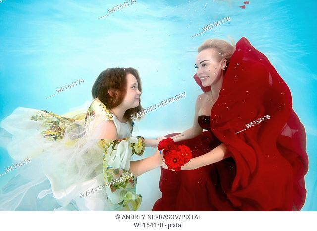 Woman in red dress with teen daughter posing under water in the pool