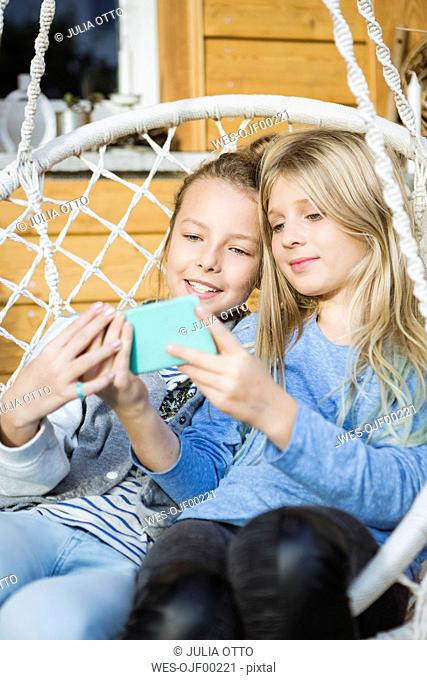 Portrait of two girls relaxing in a hanging chair taking selfie with smartphone
