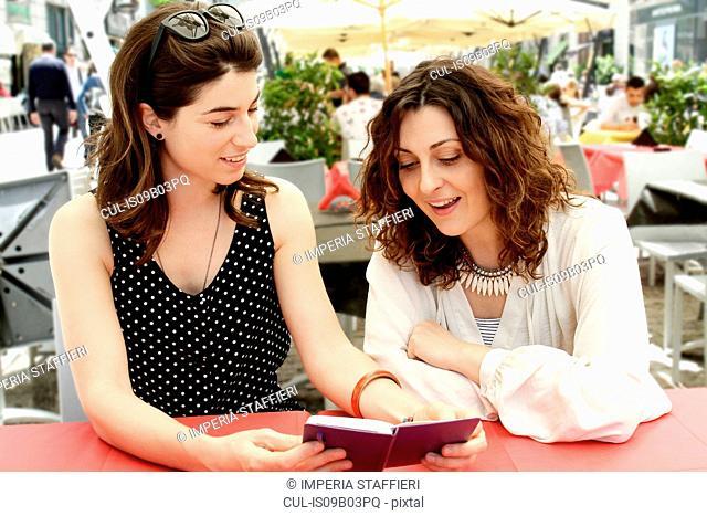 Two women reading notebook at sidewalk cafe, Milan, Italy