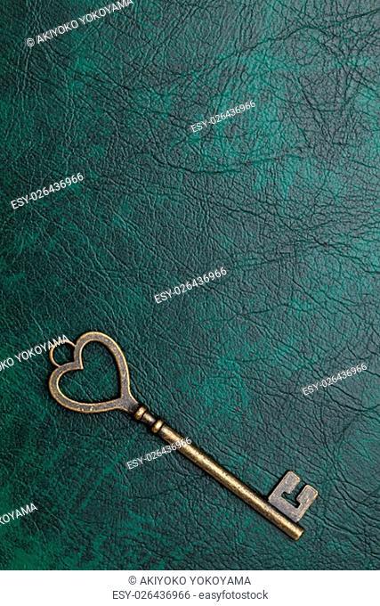 vintage key heart shape on green leather background