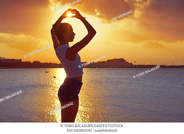 Girl silhouette at sunset heart shape in hands on the beach