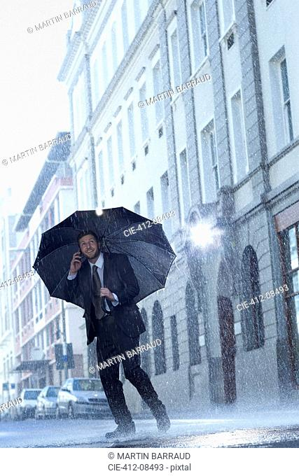 Businessman talking on cell phone under umbrella in rainy street