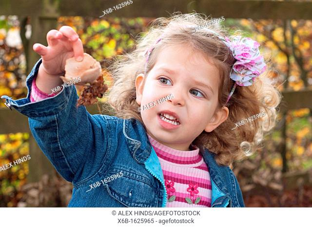 Young girl, three years old, outside during Autumn marvelling at nature and fungi mushroom she has found