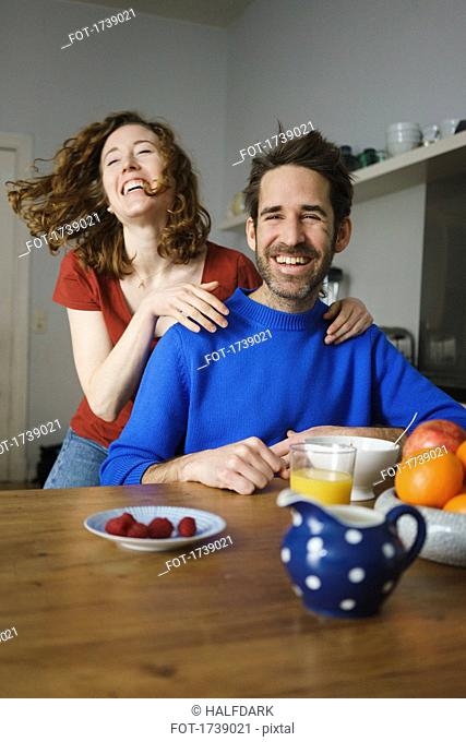 Portrait of man with cheerful woman at table with breakfast in room