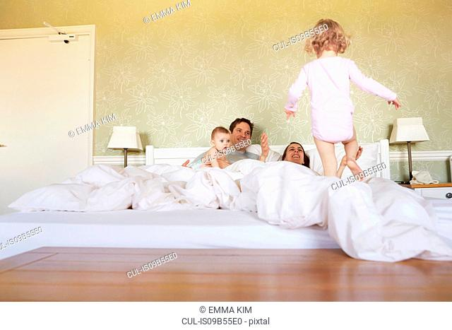 Female toddler stepping on bed with parents and baby sister