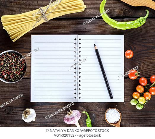 blank notebook with white sheets, raw long paste and ingredients for cooking, top view