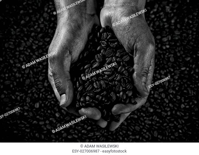 handful of coffee beans with more grains in the background - a stylized black and white film photography