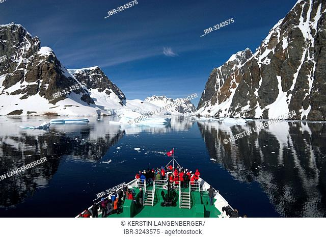 Visitors on the bow of the expedition cruise ship, MS Expedition, observing the scenery reflected in the Lemaire Channel