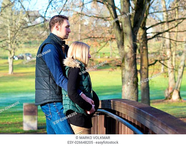 young man and his pregnant wife in the park