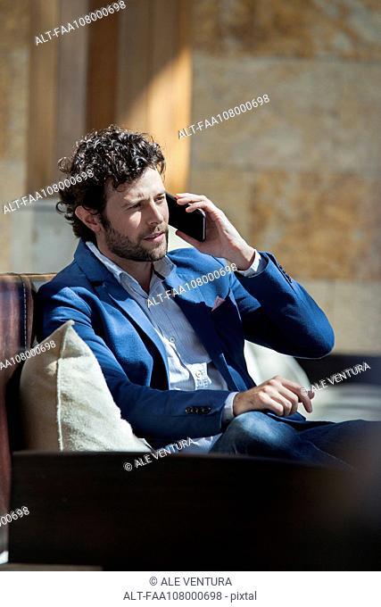 Man talking on smartphone in lobby