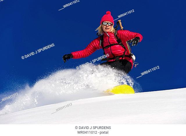 A snowboarder rides deep fresh powder snow at speed