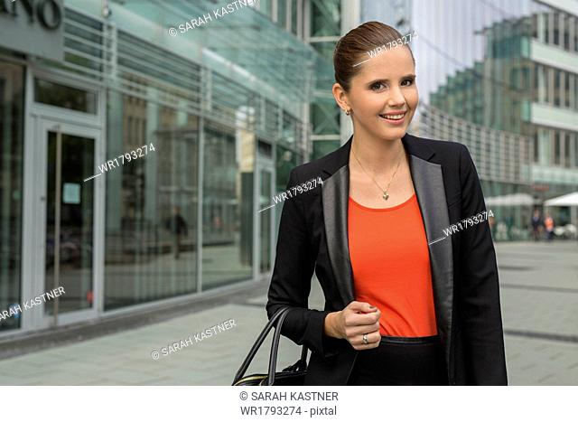 Young business woman standing in front of office building