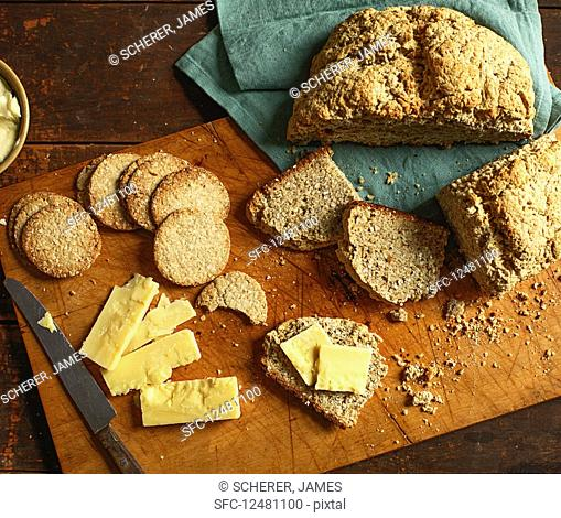 Soda bread and soda crackers with butter and cheese on a wooden chopping board