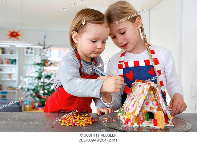 Girls at kitchen counter decorating gingerbread house together