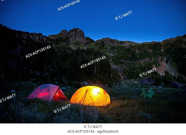 Two tents glowing at night beside Cobalt Lake. 5040 Peak in the background. Alberni-Clayoquot region, Vancouver Island, BC, Canada