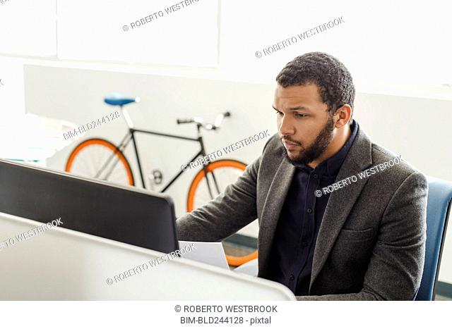 Mixed Race man using computer in office