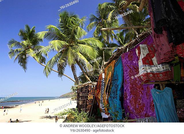 Coloured fabrics and garments hang beneath palms at beach at the long running weekly Anjuna Flea Market Goa India
