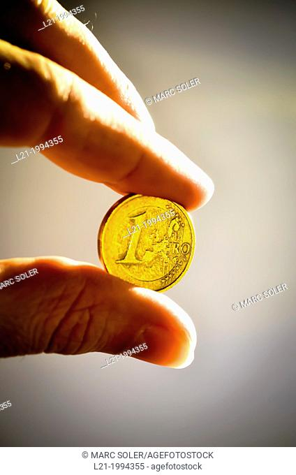 Two fingers holding a one euro coin, isolated on white background